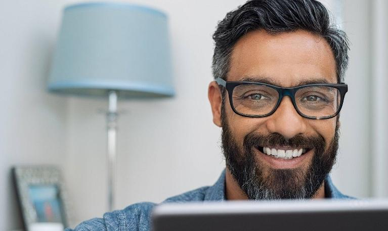 man smiling over computer screen
