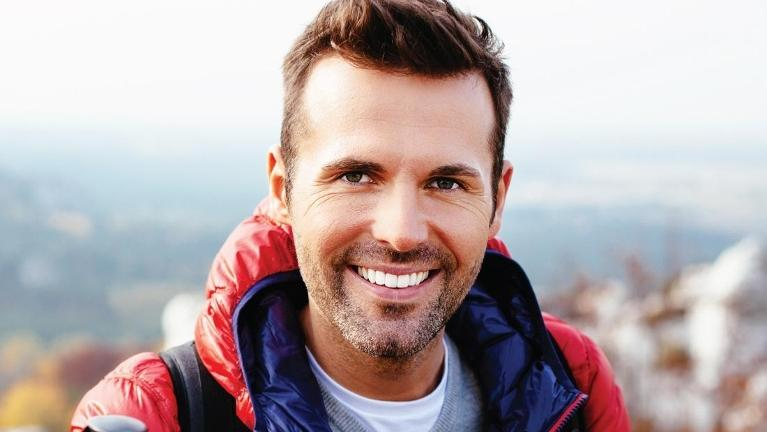 man smiling in red jacket