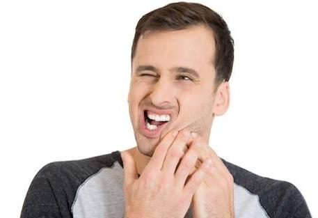 Man holding jaw from tooth pain